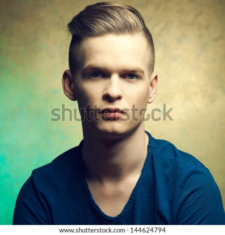 Portrait of a young man with very handsome face in blue casual t-shirt and stylish haircut posing over golden-turquoise  background. Perfect skin and hair. Hipster style. Close up. Studio shot - stock photo