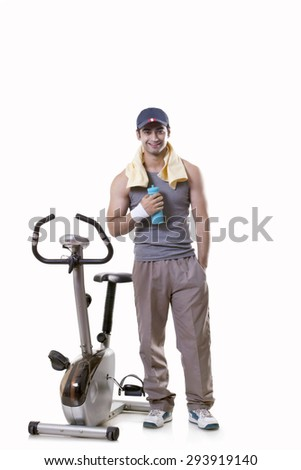 Portrait of a young man with water bottle standing next to an exercise bike over white background - stock photo
