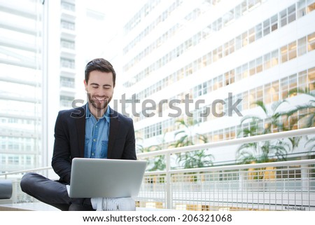 Portrait of a young man working on laptop in white building - stock photo