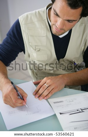 Portrait of a young man writing on a document - stock photo