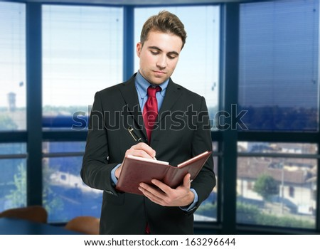 Portrait of a young man writing on his agenda