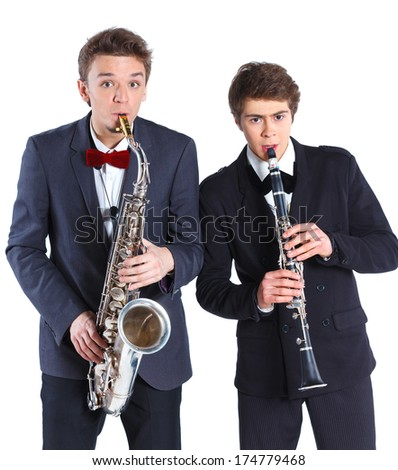 Portrait of a young mans in a suit playing on saxophone and clarinet. Isolated on background