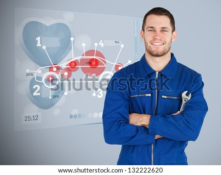 Portrait of a young mechanic next to futuristic interface with diagram - stock photo