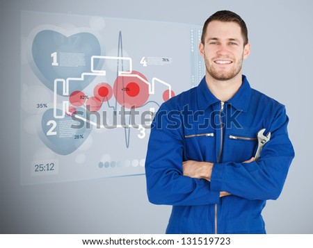 Portrait of a young mechanic with futuristic interface with engine next to him