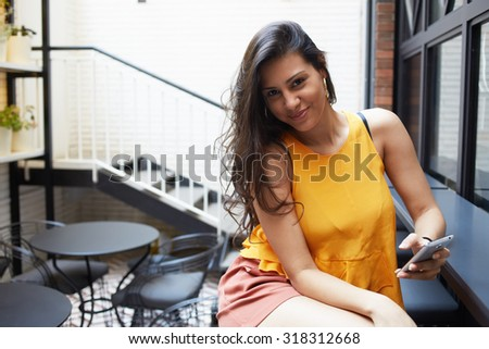 Portrait of a young modern arabic woman dressed in stylish clothes holding mobile phone while sitting in coffee shop terrace, latin female chatting on her cellphone while resting after strolling - stock photo