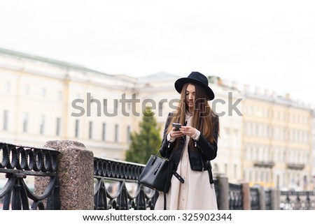 Portrait of a young modern woman dressed with style reading something on her smart phone while standing on the street, fashionable female reading message on cell telephone during strolling outside - stock photo