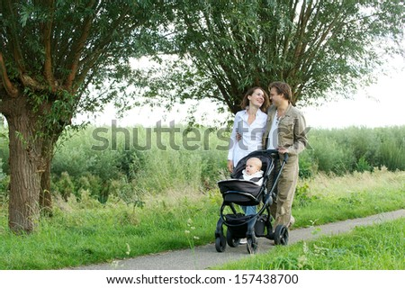 Portrait of a young mother and father walking outdoors with baby in pram - stock photo