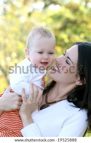 Portrait of a young mother and her blue-eyed baby boy, outdoors in a park, suitable for a variety of seasonal and family themes - stock photo