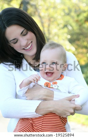 Portrait of a young mother and her blue-eyed baby boy outdoors in a park, suitable for a variety of seasonal and family themes - stock photo