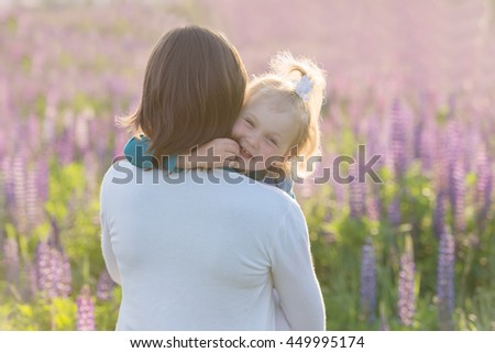 Portrait of a young mother and her little daughter on the background of the field lupine flowers - stock photo