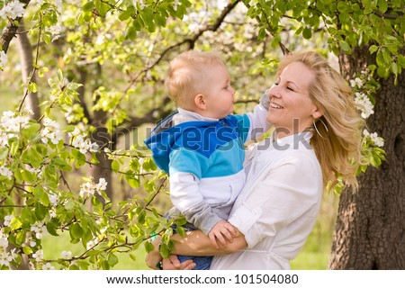 Portrait of a young mother and her son outdoors in nature at spring. - stock photo