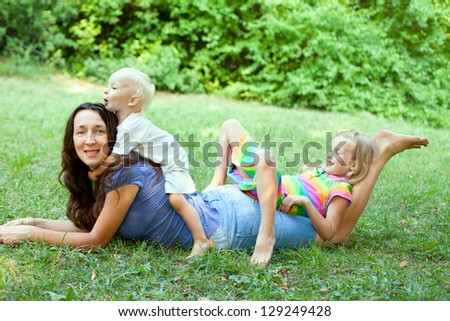 Portrait of a young mother lying on the lawn with her children sitting on her back, in the outdoors.