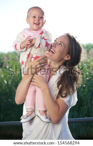 Portrait of a young mother smiling outdoors with adorable baby