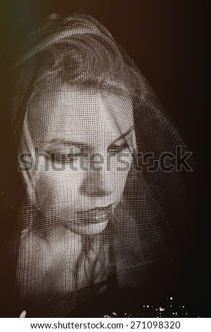 Portrait of a young mourning woman wearing veil - stock photo