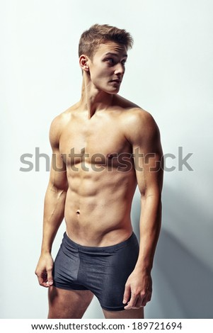 Portrait of a young muscular man in underwear looking away against white wall - stock photo