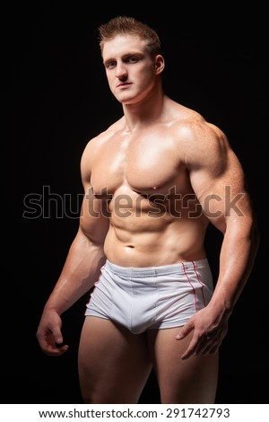 Portrait of a young muscular man in underwear standing posing over black background