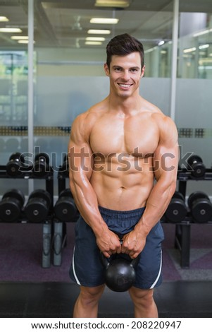 Portrait of a young muscular man lifting kettle bell in gym