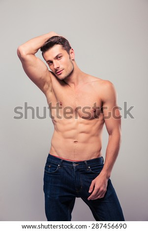 Portrait of a young muscular man posing over gray background and looking at camera - stock photo