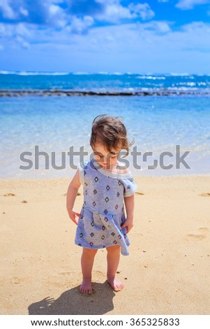 Portrait of a young one year old girl on the beach in Oahu Hawaii.
