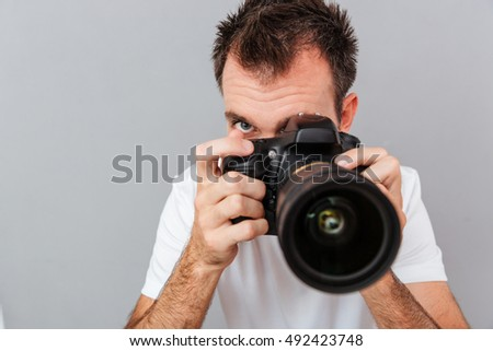 Portrait of a young photographer with camera isolated on a gray background