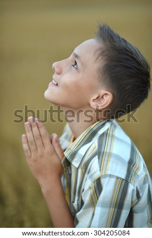 Portrait of a young  praying boy  in field - stock photo