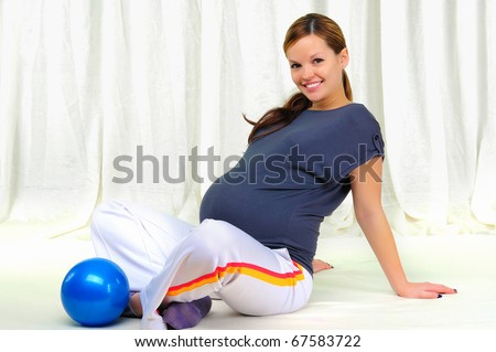 Portrait of a young pregnant girl on a light background doing exercises - stock photo