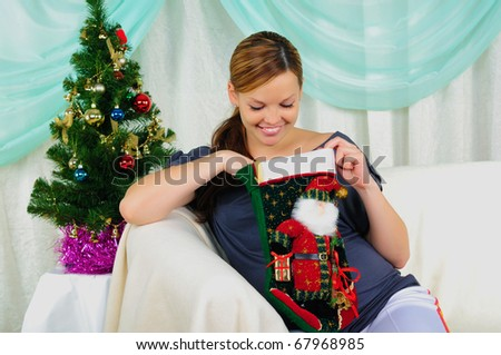 Portrait of a young pregnant girl with a gift in their hands. Happy New Year! - stock photo