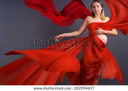 Portrait of a young pregnant woman in red dress with blowing on wind waving fabric, grey background, fashion pregnancy art