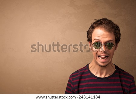 Portrait of a young pretty man with sunglasses and copyspace on brown background - stock photo