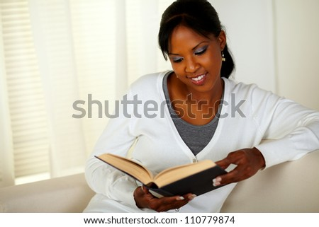 Portrait of a young pretty woman browsing a book while sitting on sofa at home indoor