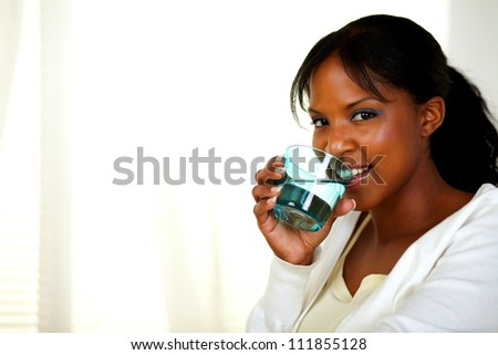 Portrait of a young pretty woman drinking healthy cool water while looking at you. With copyspace. - stock photo