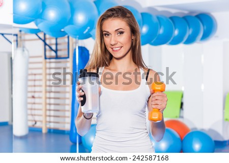 Portrait of a young pretty woman holding weight (dumbbell) and s - stock photo