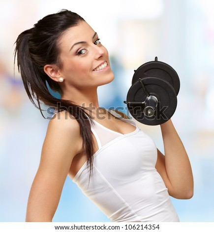 portrait of a young pretty woman holding weights and doing fitness indoor - stock photo