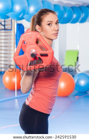 Portrait of a young pretty woman holding weights (dumbbell) and doing fitness indor. Crossfit hall. Gym shot.