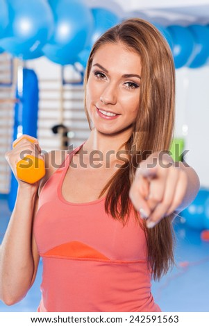 Portrait of a young pretty woman holding weights (dumbbell) and doing fitness indor. Crossfit hall. Gym shot. She is pointing camera.