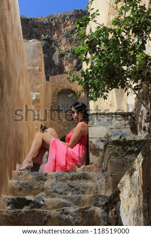 portrait of a young pretty woman with a pink dress in a beautiful place in greece - stock photo