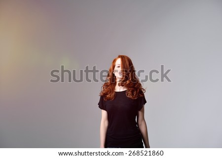 Portrait of a Young Pretty Woman with Long Red Wavy Hair Covering Half of her Face While Looking at the Camera. Captured in Studio with Gray Background a Light From the Left of the Frame. - stock photo