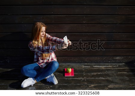Portrait of a young pretty women photographing herself for social network picture while resting outdoors, charming stylish female posing for make self portrait with her smart phone digital camera - stock photo