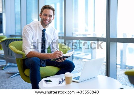 Portrait of a young professional in a modern corporate space making notes in his diary with his laptop open in front of him, and smiling confidently at the camera - stock photo