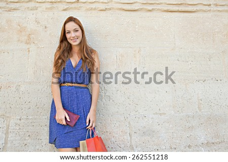 Portrait of a young professional tourist woman leaning on a plain textured stone wall on holiday, carrying shopping bags and joyfully smiling at the camera, outdoors. Travel and consumerism lifestyle.