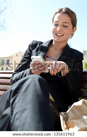 Portrait of a young professional woman sitting on a city park wooden bench while using and dialing on her smartphone, smiling.