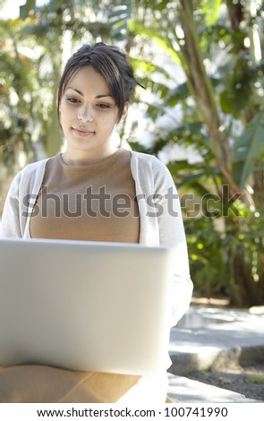 Portrait of a young professional woman using a laptop computer while sitting down in a park with golden sun light. - stock photo