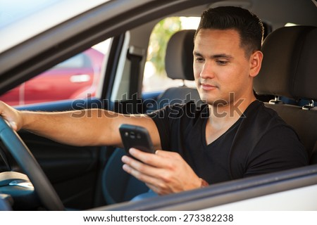 Portrait of a young reckless male driver using his cell phone behind the wheel - stock photo