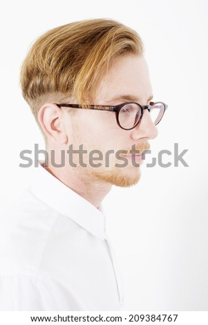 portrait of a young red-haired man with glasses and a white shirt
