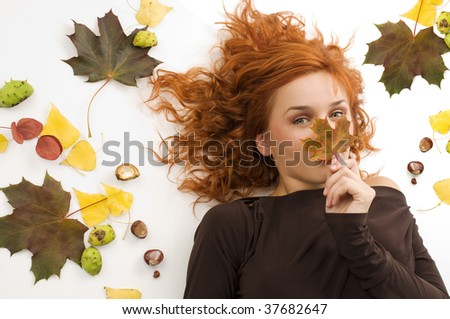 portrait of a young red haired woman hiding her nose behind an autumn leaf