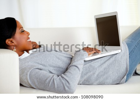 Portrait of a young relaxed woman working on laptop while is lying on sofa at home - stock photo