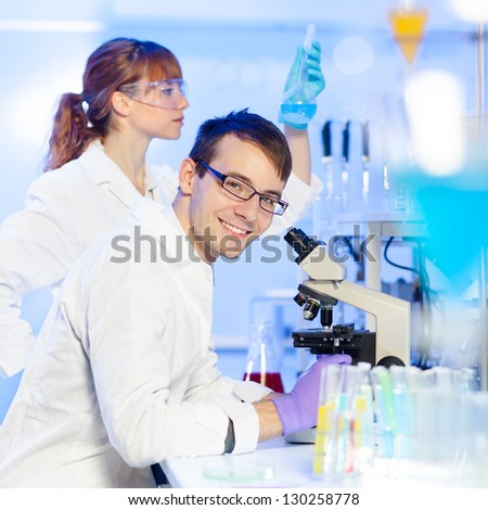 Portrait of a young researcher microscoping in the life science (forensics, microbiology, biochemistry, genetics, oncology) laboratory. Assistant scientist examining blue liquid solution in the back. - stock photo