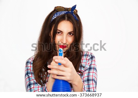 Portrait of a young retro and glamorous woman wearing pajama and holding a water sprayer in her hand posing on white background.