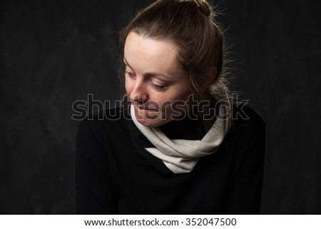 Portrait of a young sad disoriented woman , black and white image on a gray background