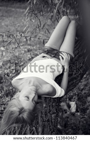 portrait of a young sad girl lying on a tree